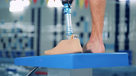 paralympics : One sportsman wears artificial leg at a pool, modern prosthesis.