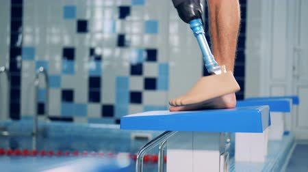 prosthesis : Man with prosthetic leg stands near a pool while training.