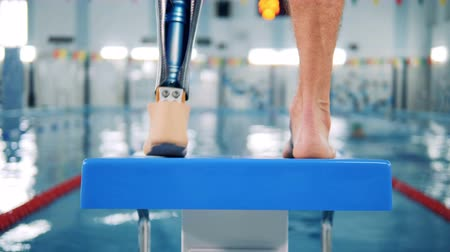 à beira da piscina : Male swimmer with bionic prosthesis warming up near a pool. Vídeos