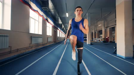 paralympic : Handicapped sprinter training on a track, bionic prosthesis.