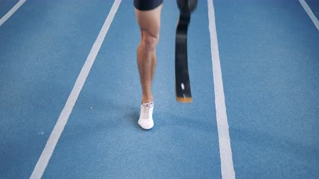 paralympic : A runner warms up on a track, wearing leg prosthesis.