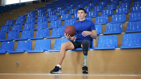 inwalida : Sportsman tosses a ball while sitting, bionic leg prosthesis. Wideo
