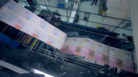 パブリッシュ : Top view of fresh printed paper moving through the industrial machine