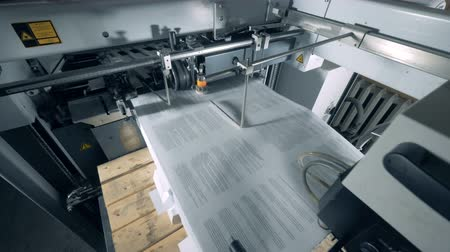 stationary : Printed pieces of paper are entering a conveyor machine Stock Footage