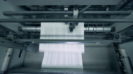stationary : Paper pages with text are getting issued by a factory mechanism in a top view Stock Footage