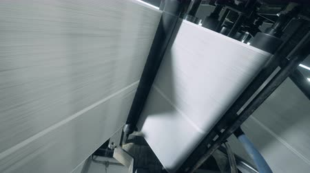ofset : Long white web of paper is moving alone the rolling machine Dostupné videozáznamy
