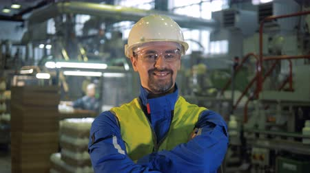 jó hangulatban : Factory worker in a hardhat is smiling at the camera