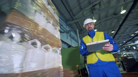 polymers : Male employee with a tablet is observing rotating pack of plastic canisters Stock Footage