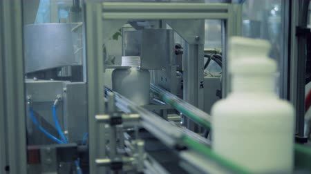 mechanically : Necks of plastic bottles are getting parted off by an industrial machine