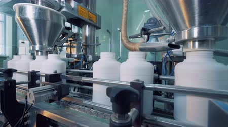 mechanically : Filling process of plastic containers carried out with factory equipment Stock Footage