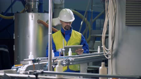 mechanically : Male technician is observing plastic bottles moving along the belt Stock Footage