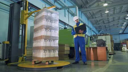 polyethylene : Polyethylene is wrapping around plastic canisters and a male worker watching it