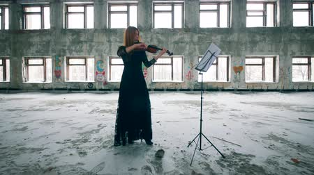 şeytan : One woman plays a violin, standing in a ruined building. Stok Video