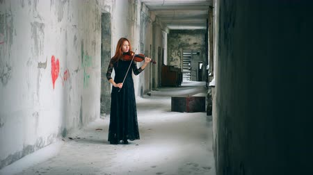 hegedűművész : Violinist plays instrument in an empty hallway of abandoned building. Stock mozgókép