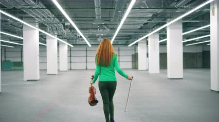 segurar : Happy violinist walks in office room, holding a violin and a fiddlestick.