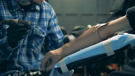 prosthesis : Person with artificial hand getting a tattoo, bionic prosthesis.