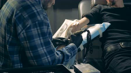 prosthesis : A tattoo master uses equipment while tattooing hand prosthesis.