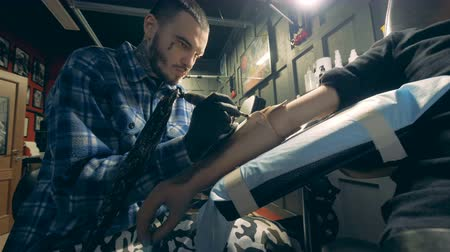 protesi : Professional tattooer drawing on a hand prosthesis, handicapped person.