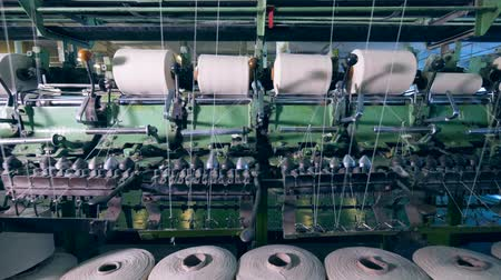 navíjení : Spools with white threads are getting mechanically unwound. Garment factory production equipment.