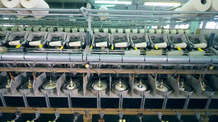 ткать : Factory machine is reeling bobbins with threads. Garment factory production equipment. Стоковые видеозаписи