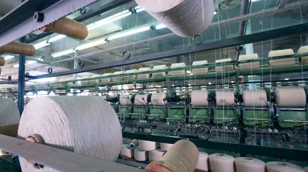 編まれた : White threads are getting mechanically relocated among reels. Textile factory equipment. 動画素材