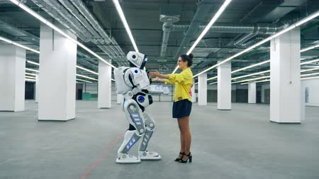 coming : Tall robot is coming to a girl and embracing her