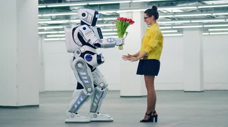 sentetik : Tall robot is giving flowers to a woman in an empty hall