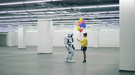 ヒューマノイド : Massive hall with a robot getting balloons from a lady