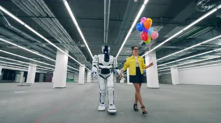 просторный : A lady with balloons is walking with a cyborg along the hall