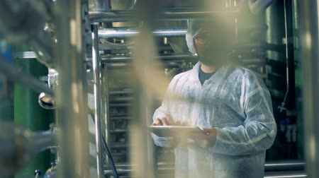 fermenting : Distillery facility with a male technician observing it and working with a tablet Stock Footage