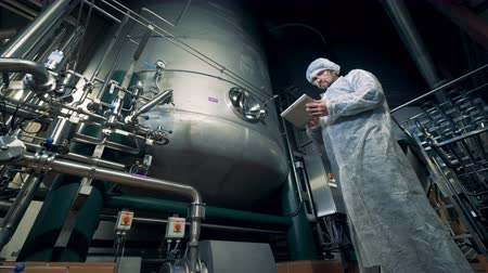 üreten : Male worker is controlling functioning process of brewing equipment Stok Video