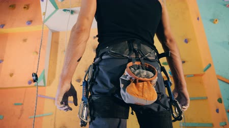 being prepared : A wall in a bouldering gym and a man with special inventory being ready to climb it
