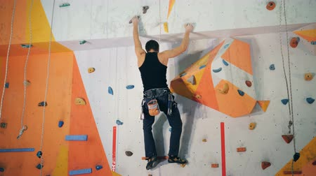 climber rock : Male climber is bouldering a wall in an artificial climbing facility