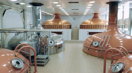 медь : Many steel tanks brew beer in a facility room at a factory.