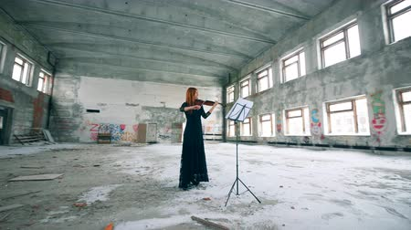 rundown : Abandoned building with a lady playing the violin