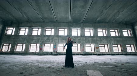 yıkık : Female violinist is playing the instrument in an unkempt building