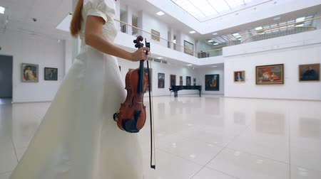 traje de passeio : Woman with a violin is walking along the art gallery