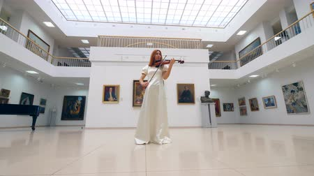 cellist : Lady in a white dress is playing the violin in the gallery hall