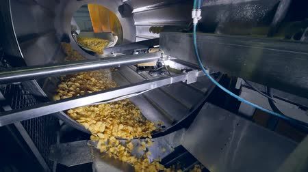 крахмал : Factory equipment rotates crisps in a machine, adding flavor enhancers.