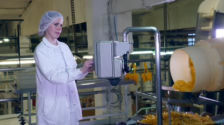 ユニット : Female worker stands in a food facility, controlling a conveyor with crisps.