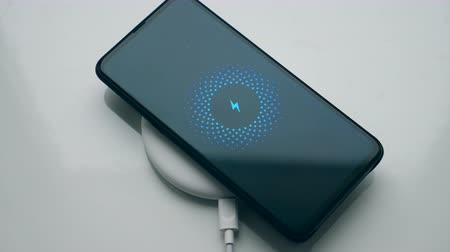 recharged : Black smartphone recharged on a wireless charging station. Wireless technology concept.