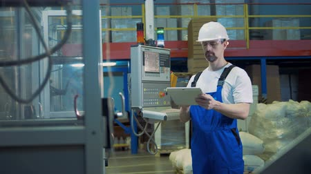 gerir : Male engineer with a tablet is inspecting industrial fabrication process Vídeos