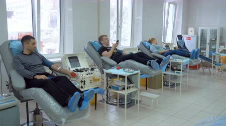 donaciones : Three patients donate blood in a modern clinic, using medical equipment. Archivo de Video