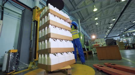 polymers : Carton boxes with plastic containers are getting stacked by male loader Stock Footage