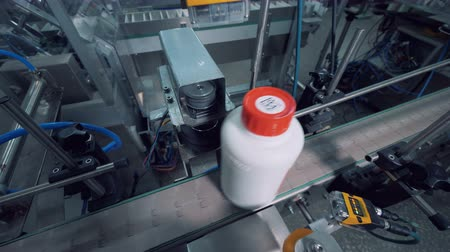 labeled : Top view of plastic bottles getting taped and marked Stock Footage