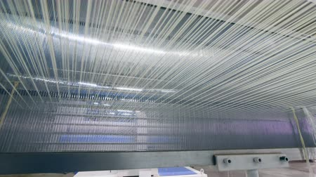automatický : Lots of strings woven on a factory machine automatically. Industrial textile factory.