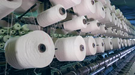 vesszőfonás : Many spools with threads spinning on a factory machine. industrial fabric production line