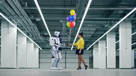 darovat : A woman gives bunch of balloons to a white droid.