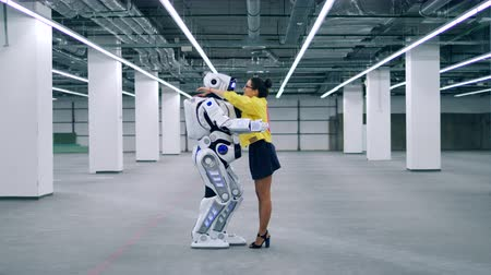 droid : Droid and a woman hug each other, standing in a room.