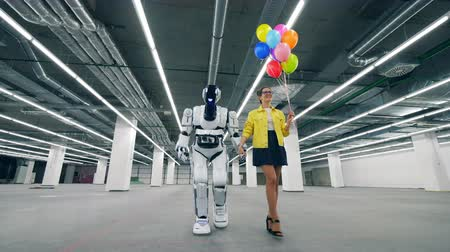 андроид : White robot walks with a woman, holding her hand.
